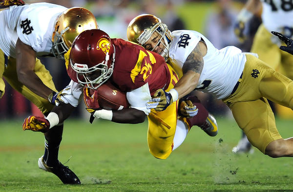 USC running back Silas Redd is brought down by Notre Dame's KeiVarae Russell, left, and Bennett Jackson in the second quarter at the Los Angeles Coliseum on Saturday, November 24, 2012.