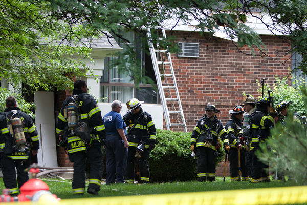 Firefighters gather outside an apartment building in the 7400 block of Woodward Avenue in Woodridge, Ill., after extinguishing a blaze.