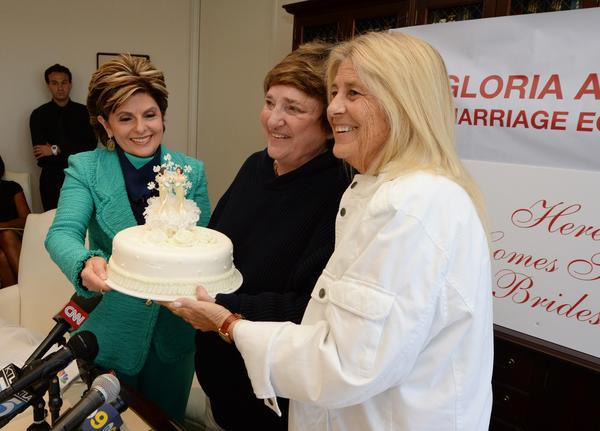 Attorney Gloria Allred, left, passes a wedding cake to Robin Tyler, center, and her wife, Diane Olson, at a news conference in Los Angeles, after the U.S. Supreme Court issued decisions on California's Proposition 8 and the federal Defense of Marriage Act.