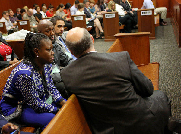 Assistant state attorney Bernie de la Rionda, with back to camera, speaks with Trayvon Martin's parents, Sybrina Fulton, left, and Tracy Martin, at the end of the lunch recess during George Zimmerman's trial in Sanford, Fla.
