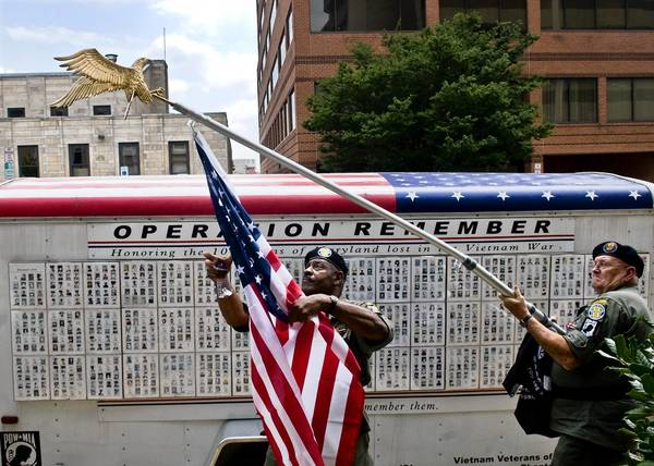 Members of the military and veterans from all wars march in and are honored in the annual Towson Area July Fourth Parade. Here, Vietnam vets Nat Richardson and Bill Tucker lower a U.S. flag after marching in the 2008 parade.