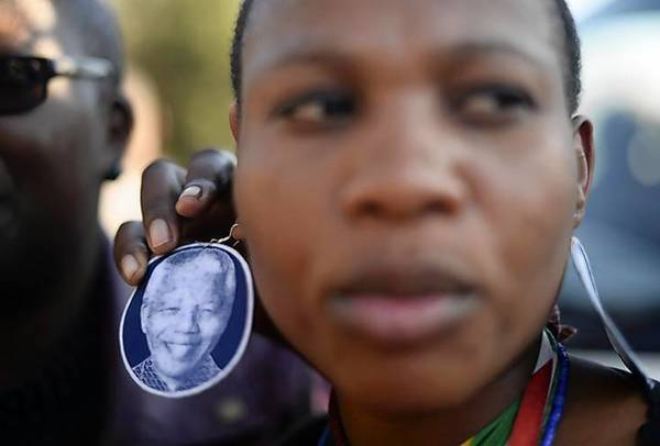 A woman wears an earring bearing the image of ailing former South African President Nelson Mandela outside the Medi-Clinic Heart Hospital where he is being treated in Pretoria.