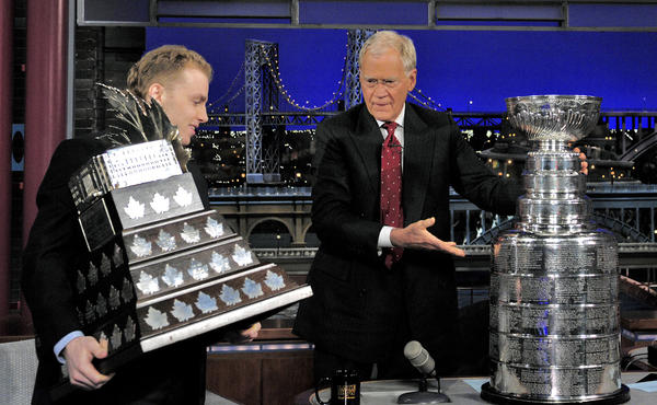 Patrick Kane holds his Conn Smythe Trophy while Late Show host David Letterman places the Stanley Cup on his desk during Wednesday's taping in New York.