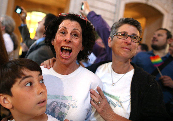 Same-sex couple Sue Rochman, center, and Robin Romdalvik, with their son Maddox Rochman-Romdalvik, celebrate in San Francisco upon hearing the U.S. Supreme Court's rulings on gay marriage.