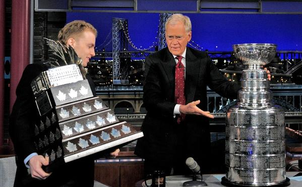 Patrick Kane carries his MVP trophy while David Letterman places the Stanley Cup on his desk during Wednesday's taping.