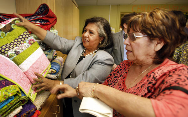 Los Angeles County Supervisor Gloria Molina, left, helps Gloria Flores place quilts in the Department of Children and Family Services Children's Welcome Center at LAC/USC, where abused or neglected children under age 10 go while a suitable foster or relative home is located for them.