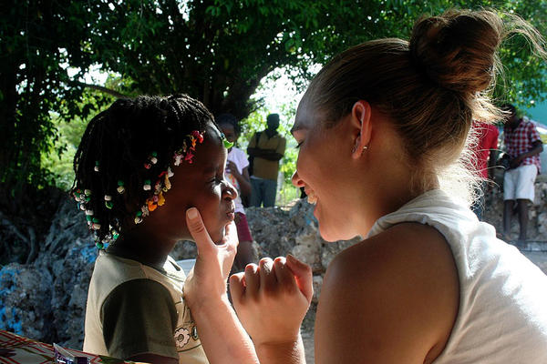 An Elevate Destinations volunteer and student playfully interact in Haiti.