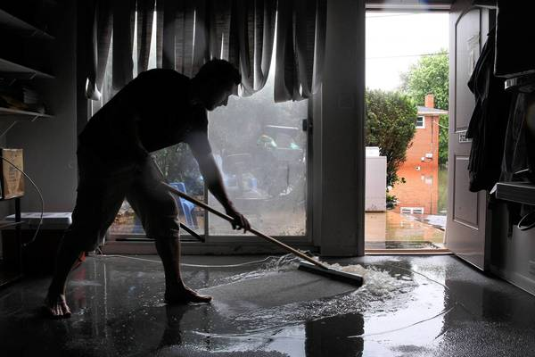 Nick Sebastian squeegees out his basement in his home on South Summit Street in Barrington on Wednesday. An estimated 8 inches of rain fell overnight, flooding several homes in the area.