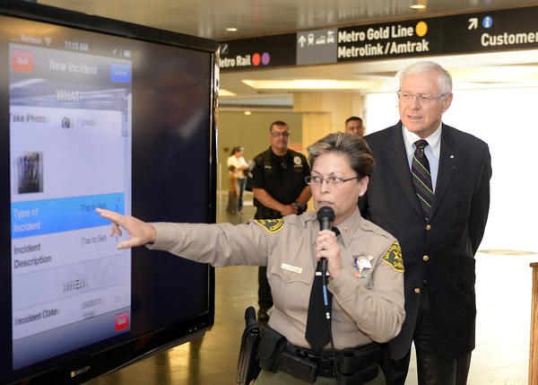 Sheriff's Cmdr. Ronene Anda and Los Angeles County Supervisor Michael Antonovich demonstrate the new Metro crime-reporting app.