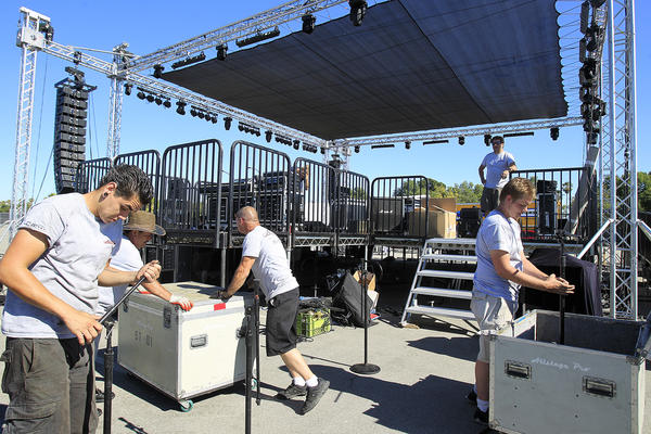 Workers prepare the main stage for the City of Costa Mesa's 60th anniversary bash on Wednesday.