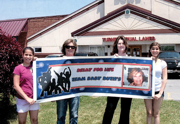 The Baby Ruths Relay for Life team representatives, from left, are Aaliyah Russ, Debra Rogers, Christie Pleasant and Alexcia Russ, who are holding the team banner outside Turner's Dual Lanes in Hagerstown.