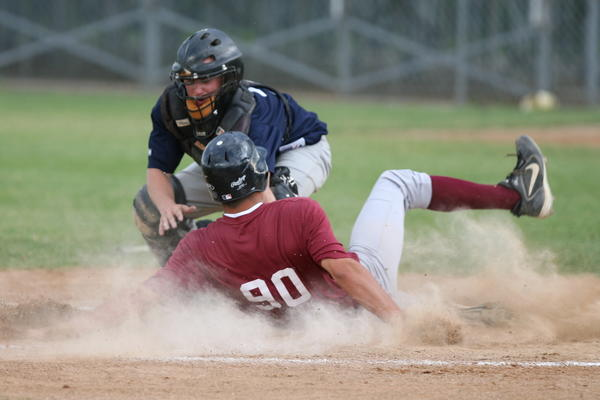 Aberdeen Circus Sports Bar catcher Josh Cunningham tries to tag out Mobridges Jesse Brown during a play at the plate at Fossum Field Wednesday night. Brown ended up scoring one of his teams 11 runs on the play, as the visitors came up with an 11-6 amateur baseball victory.