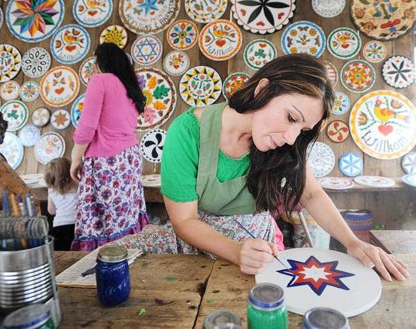 Rachel Taras of Kempton paints at the booth of Claypoole Hexsigns at the Kutztown Folk Festival in 2012.