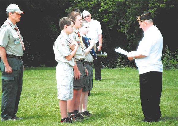 Members of Cub Scout Pack 23 and Boy Scout Troop 23, under the direction of Scoutmaster Rich Gaver, present unserviceable United States flags to Cmdr. Richard Shipley of Funkstown Post 211 American Legion, at the post's flag disposal ceremony on June 14.
