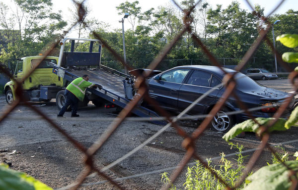 A tow truck operator loads a car onto a flatbed truck for removal from a tow yard on the 6400 block of South Bell Avenue in Chicago. Dozens of stolen cars, trucks and auto parts were recovered from the yard.
