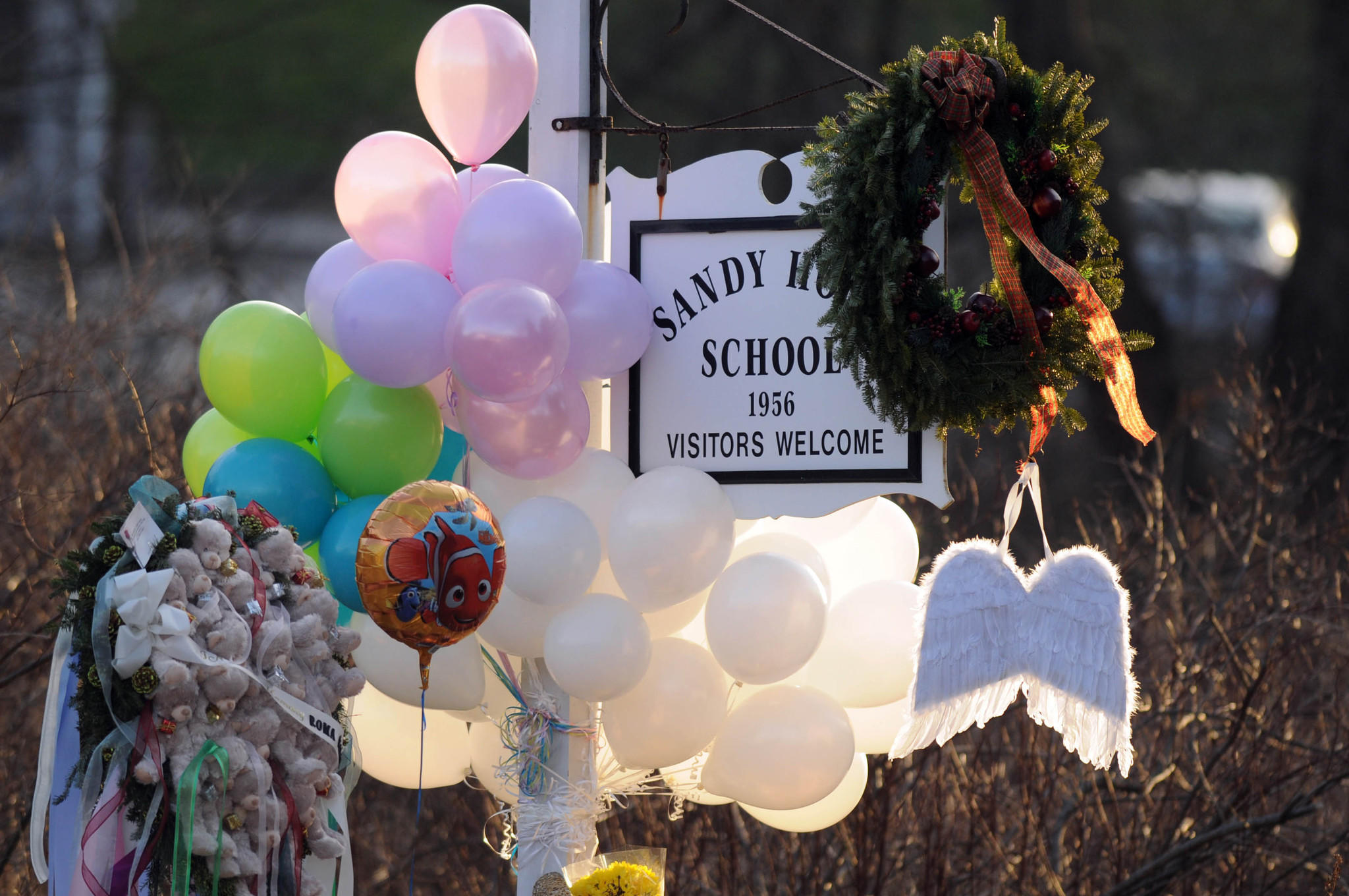 Mourners came Saturday to leave flowers, teddy bears, candles, balloons and a pair of angle wings at the Sandy Hook School sign marking the entrance to the school grounds. The makeshift memorial grew as a steady stream of mourners visited the site throughout the day.