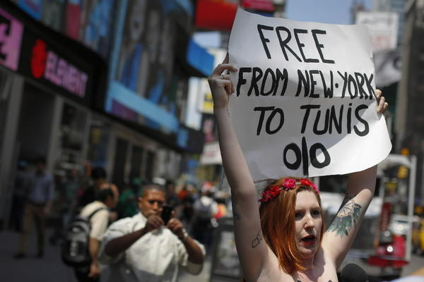 Sarah Constantin, an activist from the women's rights group FEMEN, holds up a sign during a topless protest June 20 at Times Square in New York.