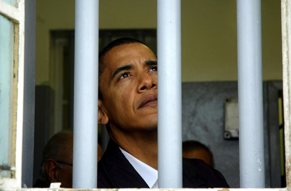 Barack Obama, then US senator for Illinois, looks out of the window of Mandela's jail cell in August 2006, on Robben Island.