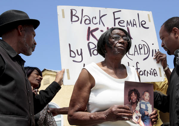 Ada Moses holds a photo of her granddaughter, Alesia Thomas, 35, and great-granddaughter as she speaks during a news conference.