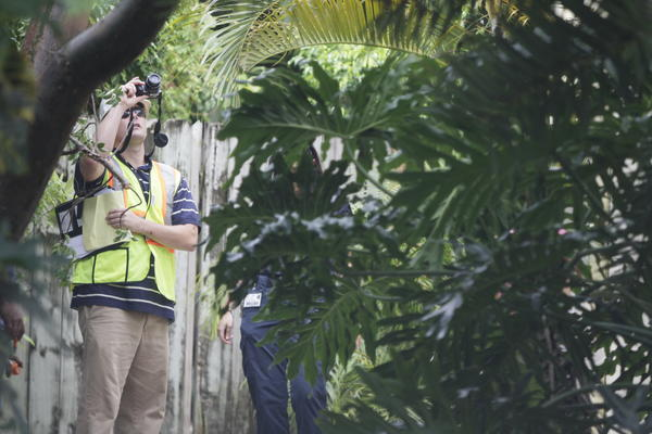 Occupational Safety and Health Administration Compliance Officer Chad Schulenberg takes photos on the side of the home at 1400 Spanish River Road on Thursday where a 21-year-old man was electrocuted in a roofing accident after lifting a ladder that touched power lines.