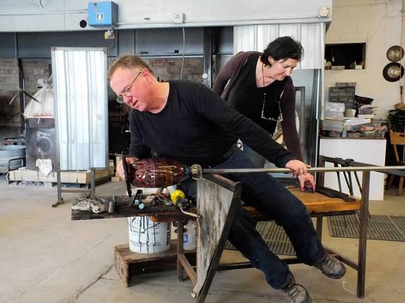 Stephanie Trenchard and Jeremy Popelka (Jerry Popelka and Stephanie Trenchard) work to form a molten piece of glass inside their Sturgeon Bay studio.