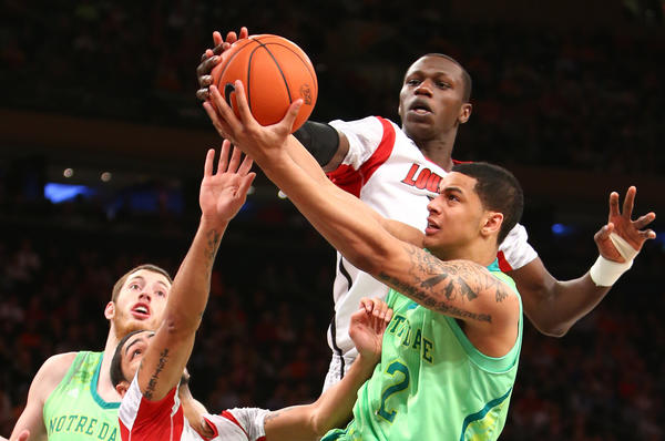 Louisville's Russ Smith and Notre Dame's Zach Auguste battle for the rebound during the first half.