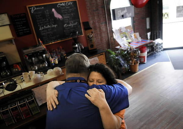 Virginia Iacobucci, the owner of the La Paloma Sabanera coffee shop, a fixture on Capitol Ave. in Hartford's Frog Hollow neighborhood, hugs one of her regular cuastomers, Zach Fraser of Manchester, who works for the Dept. of Public Health down the street. Fraser came in for his final cup of coffee before the shop closed for good Thursday.