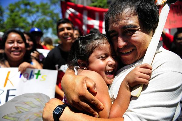 Eraclio Rojas and daughter Marisol, 5, part of a 24-hour immigration vigil in downtown Los Angeles, celebrate Senate passage of the immigration overhaul.