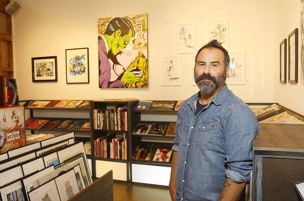 Juan Tocayo in front of his work that lines the walls in the As Issued art gallery and bookstore at The Lab in Costa Mesa.