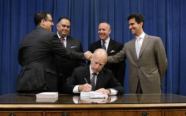 Gov. Jerry Brown signs the state budget in the presence of legislative leaders. Behind him, left to right, are Assemblymen Bob Blumenfield and John Pérez and Sens. Darrell Steinberg and Mark Leno.
