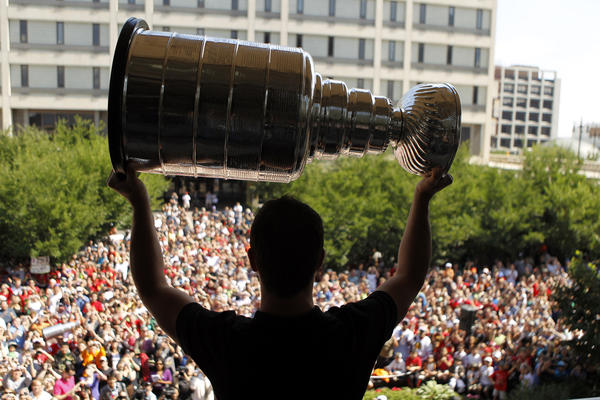 From the Queen's balcony, Jonathan Toews shows the Stanley Cup to the crowd gathered at his celebration outside City Hall in Winnipeg, Manitoba.