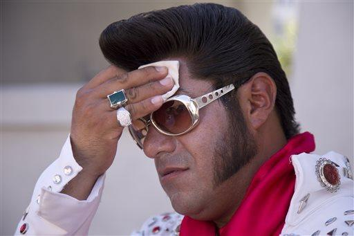 Las Vegas Elvis impersonator Cristian Morales wipes sweat from his brow in 112-degree heat on the Strip, where he was posing Thursday for photos with tourists.