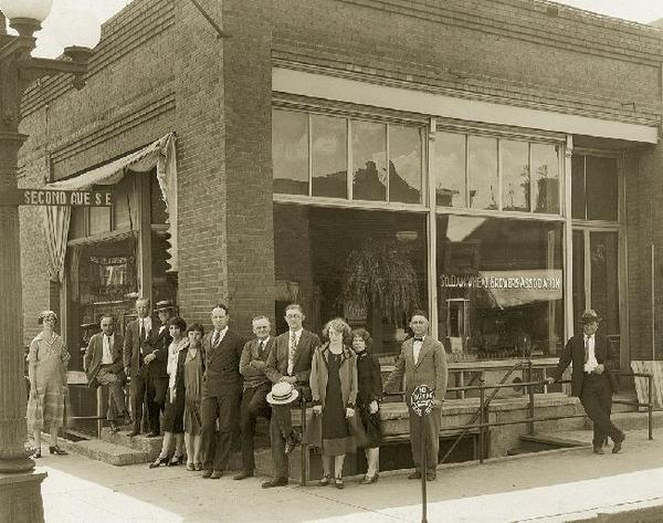In 1926, the South Dakota Wheat Growers Association's offices were at the corner of Second Avenue and Lincoln Street in Aberdeen. Staff pictured are, from left to right, Oberg Hafnor, C.W. Croes, Rudy Freeman, Robert Mackin, Bernice Jarman, (unknown employee), Harman King, Richard Weir, Otto Wiedebush, Helen Geer, Katherine Barnett, Bern Dickinson and a passerby.