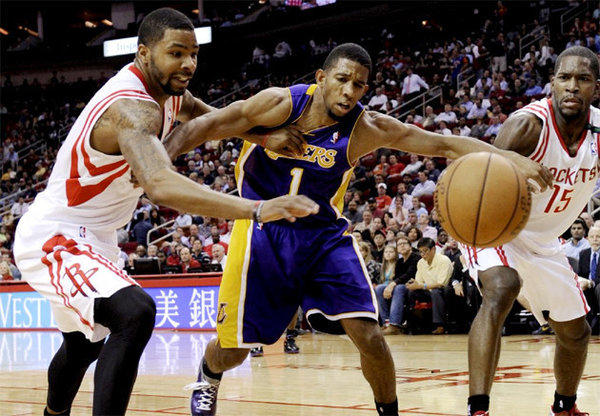 Lakers point guard Darius Morris battles for a loose ball against Houston Rockets forward Marcus Morris and guard Toney Douglas.