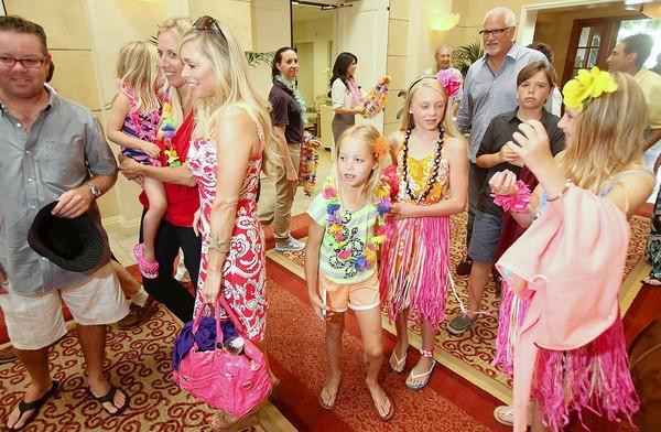 Guests pour into the party including Janice Hess, with pink bag, and her daughter Kate, and friend Kelley Carr, in the hula skirts, during the Balboa Bay Club's 65th Anniversary Luau, Thursday.