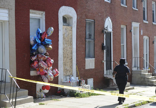 A Baltimore police officer walks by a makeshift shrine on the 900 block of Bennett Place in the Harlem Park neighborhood.