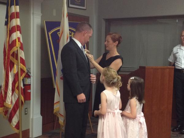 West Hartford Police officer Bill Norton was promoted to detective Friday. His wife, Dianne, is seen pinning him while daughters Kylie and Kaelyn look on.