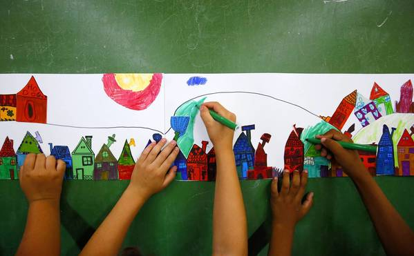 Children taught by the Igazgyongy (Pearl) art education foundation work on a picture of a village, at a school in Berettyoujfalu, eastern Hungary.