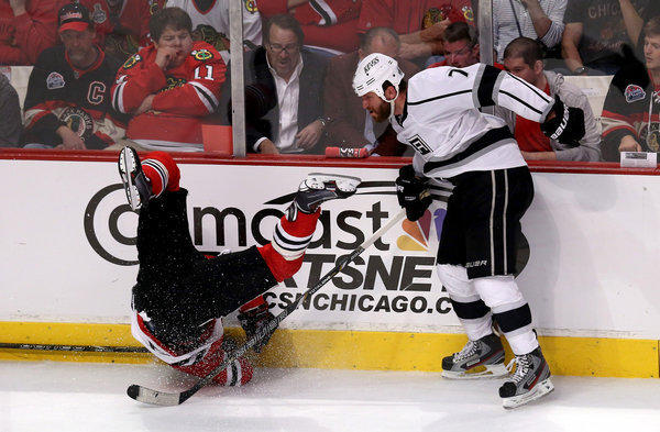 Kings defenseman Rob Scuderi (7) drops Blackhawks forward Patrick Sharp with a check along the side boards in the second period of Game 2 of the Western Conference finals.