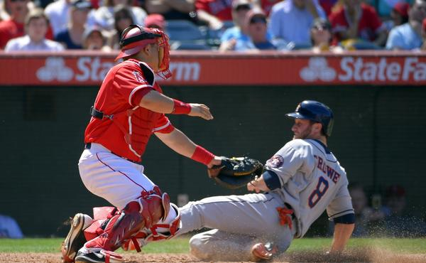 Angels catcher Hank Conger, left, tags out Houston's Trevor Crowe at home plate during a game on June 2. Conger has made a difference for the Angels behind home plate.