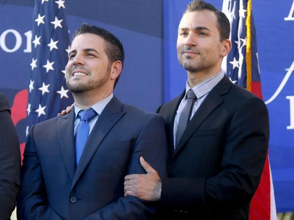 Paul Katami of Burbank, right and his partner Jeff Zarillo, left celebrate after the Supreme Court struck down a key part of the federal Defense of Marriage Act, during a rally in West Hollywood, on Wednesday, June 26, 2013.