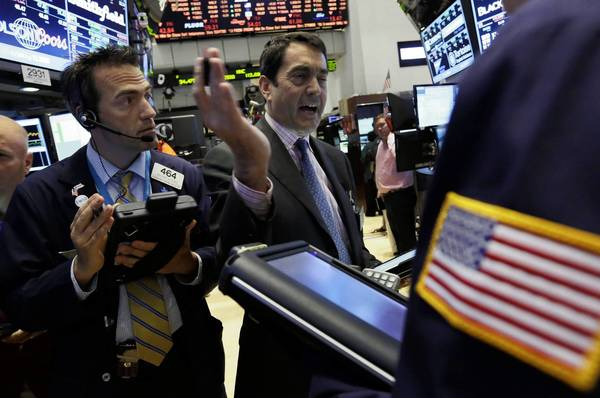 Gregory Rowe, left, and Mark Muller, center, work on the floor of the NYSE. U.S. stocks saw double-digit gains for the first half of the year.