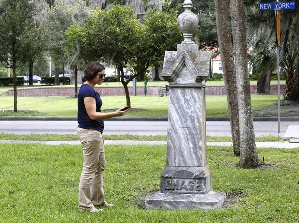 City of Winter Park cemeteries manager Janna Baumann uses her smartphone at Palm Cemetery. A new app will allow visitors to Winter Park cemeteries to find the graves of dearly departed loved ones and pull up biographical information.