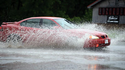 A car moves through high water along Pleasant Avenue at the intersection of East Main Street in Somerset on Friday.