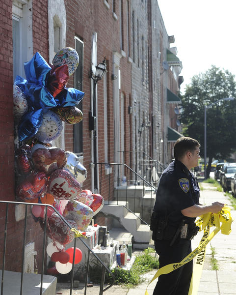 A Baltimore police officer removes crime scene tape at the end of the crime scene investigation for a shooting that ocurred earlier this morning on the 900 block of Bennett Place in the Harlem Park neighborhood of west Baltimore.