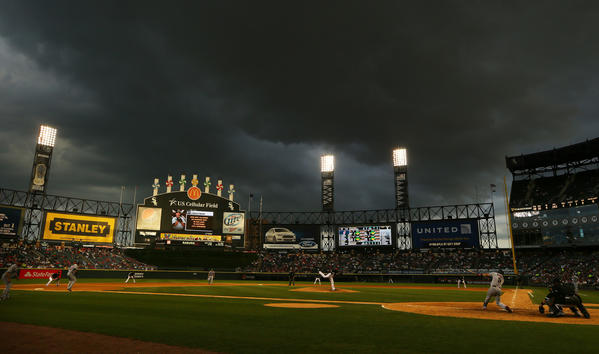 Storm clouds loom overhead during the first game of a doubleheader.