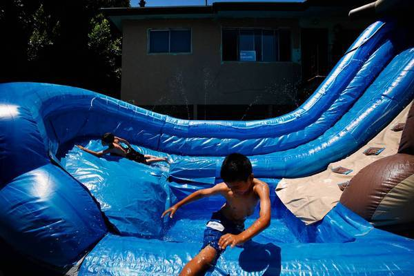On a very hot day in L.A., David Murillio, 8, left, and Joshua Rodriguez, 9, cool off in a two-story inflatable pool in Boyle Heights. The boys were on their way to Pecan Recreation Center when they saw their neighbor's rented pool and jumped in. The last significant heat wave to hit Southern California was five years ago, a National Weather Service specialist said.