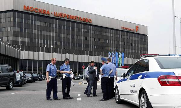 Police stand watch outside Sheremetyevo International Airport in Moscow, where U.S. National Security Administration leaker Edward Snowden is thought to be holed up in a transfer area. His father, Lonnie, says he is trying to broker a deal to return his son to the U.S.