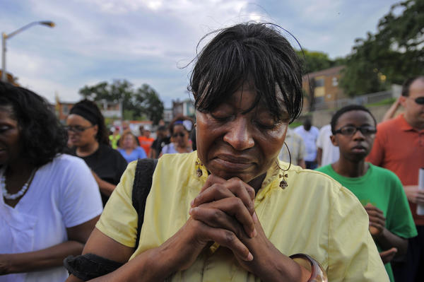 "Soan Evans prays on Gertrude Court in the place known as ""Chocolate City,"" as the ""Bless Baltimore Prayer Motorcade,"" -- in response to a rash of overwhelming bloodshed and violence -- hits another portion of the city Friday."