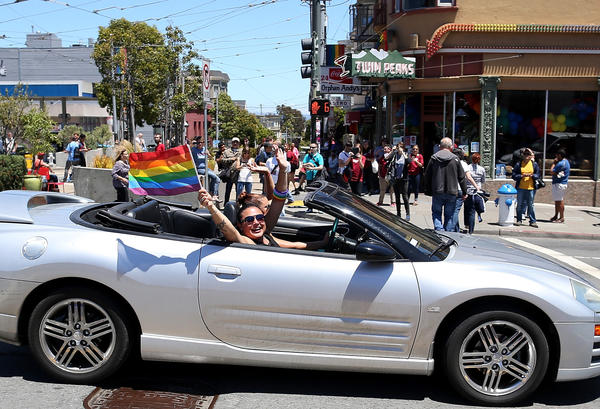 Same-sex marriage supporters wave pride flags from a car Wednesday as they drive by the corner of Market and Castro in San Francisco.